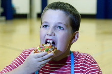 Paul Fraughton | The Salt Lake Tribune Elijah Martinez takes a big bite from his healthy English Muffin Pizza he made at a cooking class at the the Murray Boys and Girls Club.
