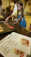 Paul Fraughton | The Salt Lake Tribune Savannah Wendelboe, 8, makes an English muffin pizza on Oct. 1, 2012.