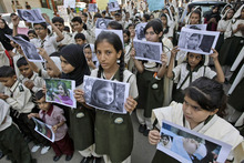 Pakistani students hold pictures of 14-year-old schoolgirl Malala Yousufzai, who was shot last Tuesday by the Taliban for speaking out in support of education for women, during a protest condemning the attack, in Karachi, Pakistan, Saturday, Oct. 13, 2012. (AP Photo/Fareed Khan)