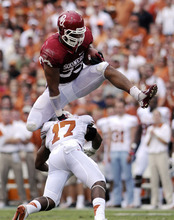 Oklahoma fullback Trey Millard hurdles Texas saferty Adrian Phillips during the first quarter of an NCAA college football game at the Cotton Bowl Saturday, Oct. 13, 2012, in Dallas. (AP Photo/The Daily Texan, Lawrence Peart)
