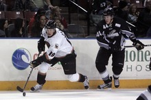 Kim Raff   The Salt Lake Tribune (left) Utah Grizzlies player Colin Vock takes control of the puck as Idaho Steelheads player Scott Todd follows during the Grizzlies home opener at the Maverick Center in West Valley City, Utah on October 13, 2012.
