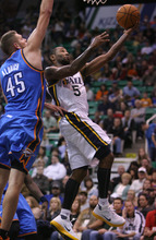 Steve Griffin | The Salt Lake Tribune   Utah's Mo Williams glides past the Thunder's Cole Aldrich for a layup during second half action in the Jazz Thunder preseason game and EnergySolutions Arena in Salt Lake City, Utah Friday October 12, 2012.