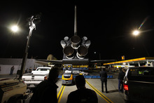 As work lights illuminate the scene, workers and spectators view the engines of the space shuttle Endeavour outside of Randy's Donuts as it waits to cross the 405 freeway in Inglewood, Calif., Friday, Oct. 12, 2012. Endeavour's 12-mile road trip kicked off shortly before midnight Thursday as it moved from its Los Angeles International Airport hangar en route to the California Science Center. (AP Photo/Patrick T. Fallon)