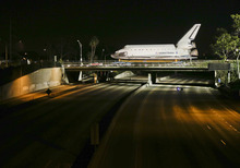 The space shuttle Endeavour makes it's way down Manchester Blvd. over a closed 405 fwy in Inglewood, Calif., Friday, Oct. 12, 2012. Endeavour's 12-mile road trip kicked off shortly before midnight Thursday as it moved from its Los Angeles International Airport hangar en route to the California Science Center, its ultimate destination. (AP Photo/Chris Carlson)