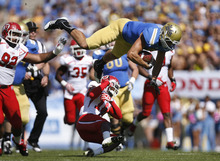 Scott Sommerdorf  |  The Salt Lake Tribune              UCLA Bruins tight end Joseph Fauria (8) is knocked flying by a hit by Utah Utes defensive back Eric Rowe (18) during first half play. Utah plays UCLA in Pasadena, Saturday, October 13, 2012.