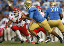 Scott Sommerdorf  |  The Salt Lake Tribune              Utah Utes linebacker LT Filiaga (42) tries to contain UCLA Bruins quarterback Brett Hundley (17) during this third quarter play. Often Hundley would escape intense pressure in the pocket, and make big gains on the Utah defense. UCLA defeated Utah 21-14 in Pasadena, Saturday, October 13, 2012.