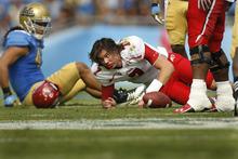 Scott Sommerdorf  |  The Salt Lake Tribune              Utah Utes quarterback Travis Wilson (7) lost his helmet on this run at the 11:41 mark of the third quarter. UCLA defeated Utah 21-14 in Pasadena, Saturday, October 13, 2012.