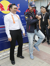 Red Bull driver Sebastian Vettel, right, of Germany performs with South Korean rapper PSY and his