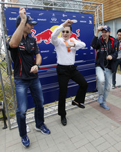 Red Bull driver Mark Webber, left, of Australia and his teammate Sebastian Vettel, right, of Germany perform with South Korean rapper PSY, centre, and his