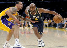 Utah Jazz guard Jamaal Tinsley (6) gets by Los Angeles Lakers center Robert Sacre (50) as he drives to the basket in the first half of an NBA preseason basketball game, Saturday, Oct. 13, 2012, in Los Angeles. (AP Photo/Gus Ruelas)