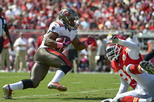 Tampa Bay Buccaneers running back Doug Martin (22) makes a move around Kansas City Chiefs outside linebacker Tamba Hali, right, during the first half of an NFL football game, Sunday, Oct. 14, 2012, in Tampa, Fla. (AP Photo/Phelan M. Ebenhack)