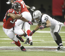 Atlanta Falcons running back Michael Turner (33) runs as Oakland Raiders outside linebacker Philip Wheeler (52) defends during the first half of an NFL football game, Sunday, Oct. 14, 2012, in Atlanta. (AP Photo/John Bazemore)
