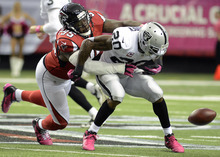 Atlanta Falcons defensive tackle Jonathan Babineaux (95) hits Oakland Raiders running back Darren McFadden (20) as McFadden fumbles the ball during the first half of an NFL football game on Sunday, Oct. 14, 2012, in Atlanta. (AP Photo/Billy Weeks)