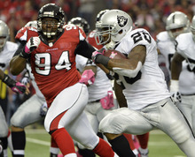 Oakland Raiders running back Darren McFadden (20) runs up field as Atlanta Falcons defensive tackle Peria Jerry (94) defends during the first half of an NFL football game, Sunday, Oct. 14, 2012, in Atlanta. (AP Photo/Rich Addicks)