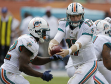 Miami Dolphins quarterback Ryan Tannehill (17) fakes a handoff to running back Reggie Bush (22) during the first half of an NFL football game against the St. Louis Rams, Sunday, Oct. 14, 2012 in Miami. (AP Photo/Lynne Sladky)