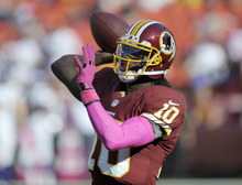 Washington Redskins quarterback Robert Griffin III throws during warm ups before an NFL football game against the Minnesota Vikings Sunday, Oct. 14, 2012, in Landover, Md. (AP Photo/Cliff Owen)
