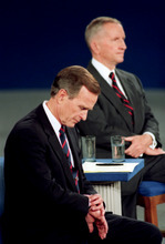 FILE - In this Oct. 15, 1992, file photo President George H.W. Bush looks at his watch during the 1992 presidential campaign debate with other candidates, Independent Ross Perot, top, and Democrat Bill Clinton, not shown, at the University of Richmond, Va. The