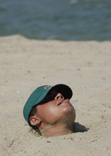 Johnny Hernandez of Fort Lauderdale, Fla., attempts to adjust his visor with his tongue while being buried up to his neck in sand while enjoying a day at the beach Sunday, Sept. 2, 2007, in Lauderdale-By-The-Sea, Fla. (AP Photo/Wilfredo Lee)