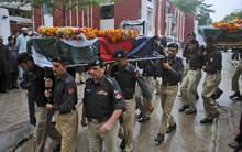 Pakistani police officers carry the bodies of fellow officers, who were killed by militants, during their funeral procession, in Peshawar, Pakistan, Monday, Oct. 15, 2012. A Pakistani official says over 100 militants attacked a police station in the northwest late on Sunday night, killing several policemen and beheading two of them. (AP Photo/Mohammad Sajjad)