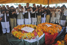 Pakistani police officers and officials pray next to the bodies of policemen who were killed by militants, during their funeral in Peshawar, Pakistan, Monday, Oct. 15, 2012. A Pakistani official says over 100 militants attacked a police station in the small town of Matni, near Peshawar, late on Sunday night, killing several policemen and beheading two of them. (AP Photo/Mohammad Sajjad)