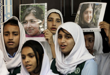 Pakistani students sing as they hold pictures of 14-year-old schoolgirl Malala Yousufzai, who was shot last Tuesday by the Taliban for speaking out in support of education for women, during a tribute at the Pakistani Embassy in Abu Dhabi, United Arab Emirates. Pakistan airlifted a 14-year-old activist who was shot and seriously wounded by the Taliban to the United Kingdom for treatment Monday, a move that will give her access to the specialized medical care she needs to recover and also protect her from follow-up attacks threatened by the militants. (AP Photo/Kamran Jebreili)