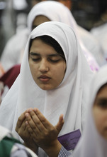 A Pakistani student prays for 14-year-old schoolgirl Malala Yousufzai, who was shot last Tuesday by the Taliban for speaking out in support of education for women, during a tribute at the Pakistani Embassy in Abu Dhabi, United Arab Emirates. Pakistan airlifted a 14-year-old activist who was shot and seriously wounded by the Taliban to the United Kingdom for treatment Monday, a move that will give her access to the specialized medical care she needs to recover and also protect her from follow-up attacks threatened by the militants. (AP Photo/Kamran Jebreili)