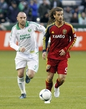 Real Salt Lake midfielder Kyle Beckerman, right, carries the ball ahead of Portland Timbers forward Kris Boyd during the first half of their MLS soccer game  in Portland, Ore., Saturday, March 31, 2012.(AP Photo/Don Ryan)