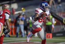 New York Giants wide receiver Victor Cruz (80) catches a 6-yard touchdown pass next to San Francisco 49ers cornerback Carlos Rogers during the second quarter of an NFL football game in San Francisco, Sunday, Oct. 14, 2012. (AP Photo/Mark J. Terrill)