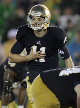 Notre Dame quarterback Tommy Rees (11) talks to teammates during overtime of an NCAA college football game against Stanford in South Bend, Ind., Saturday, Oct. 13, 2012. Notre Dame won in overtime 20-13. (AP Photo/Nam Y. Huh)