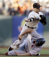 San Francisco Giants second baseman Marco Scutaro grimaces as his leg is caught under a sliding St. Louis Cardinals' Matt Holliday on a double play attempt during the first inning of Game 2 of baseball's National League championship series Monday, Oct. 15, 2012, in San Francisco. (AP Photo/Ben Margot)