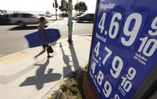 FILE - In this Friday, Oct. 5, 2012, file photo, a boogie boarder walks past a sign displaying high gas prices in Laguna Beach, Calif. Higher gas costs drove up U.S. consumer prices in September for the second straight month. But outside energy, there was little sign of inflation. (AP Photo/Chris Carlson)