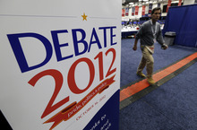 A worker walks past a sign in the media filing center before Tuesday's presidential debate between President Barack Obama and Republican presidential candidate, former Massachusetts Gov. Mitt Romney, Monday, Oct. 15, 2012, at Hofstra University in Hempstead, N.Y. (AP Photo/Charlie Neibergall)