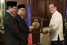Rouelle Umali  |  The Associated Press Philippine President Benigno Aquino III, right, receives a gong from Moro Islamic Liberation Front (MILF) Chairman Al Haj Murad, center, and MILF Peace Panel chief Mohagher Iqbal, left, before the historic signing of the framework agreement between the Philippine government and the MILF at the Malacanang Presidential Palace in Manila, Philippines, on Monday Oct. 15, 2012. Muslim rebels and the Philippine government overcame decades of bitter hostilities and took their first tentative step toward ending one of Asia's longest-running insurgencies with the ceremonial signing of a preliminary peace pact Monday that both sides said presented both a hope and a challenge.