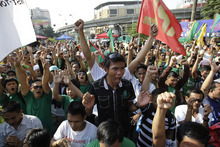 Filipino Muslims celebrate after hearing news of the signing of a preliminary peace pact between the government and the nation's largest Muslim rebel group during a rally outside the gates of the Malacanang presidential palace in Manila, Philippines on Monday Oct. 15, 2012. Muslim rebels and the Philippine government overcame decades of bitter hostilities and took their first tentative step toward ending one of Asia's longest-running insurgencies with the ceremonial signing of a preliminary peace pact Monday that both sides said presented both a hope and a challenge. (AP Photo/Aaron Favila)