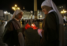Two nuns light their candles at the beginning of a procession to mark the 50th anniversary of the Second Vatican Council - the church meetings that modernized the Catholic Church but whose true results are still hotly debated - in St. Peter's square, at the Vatican, Thursday, Oct. 11, 2012. Pope Benedict XVI denounced the