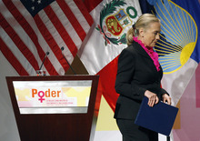 U.S. Secretary of State Hillary Rodham Clinton walks away from a lectern bearing the Spanish word,