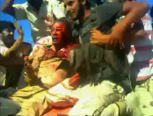 FILE - In this file image made from amateur video provided by the Libya Youth Movement and filmed on Thursday, Oct. 20, 2011, Moammar Gadhafi, center, is surrounded by Libyan fighters in Sirte, Libya. Libyan rebels appear to have