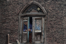 Kashmiri Muslim women look out from a window as residents protest in Srinagar, India, Wednesday, Oct. 17, 2012. Dozens of residents  blocked traffic and protested against the government decision to hike electricity bills and for capping the number of subsidized cooking gas cylinders at six a year. (AP Photo/ Dar Yasin)