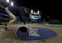 A grounds crew member rolls up the on-deck circle mat during a rain delay at Game 4 of the American League championship series between the Detroit Tigers and New York Yankees Wednesday, Oct. 17, 2012, in Detroit. (AP Photo/Paul Sancya )