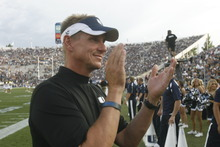 Tribune file photo   Aggie head coach Gary Andersen cheers as his team takes the field for the game against BYU in Provo in September.