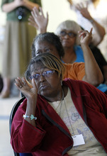 In this photo taken Sept. 20, 2012, Stella Surratt, foreground, and other raise their hands in response to a question during HIV class at the Edgewood Senior Apartment Building in Washington. Washington seniors are used to talking about a host of health issues. Alzheimer's. Diabetes. High cholesterol. Now officials in the nation's capital are asking seniors to think about a different disease: HIV.  (AP Photo/Ann Heisenfelt)