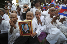 People pray upon the arrival of the casket carrying the body of former King Norodom Sihanouk arriving at the Royal Palace in Phnom Penh, Cambodia, Wednesday Oct. 17, 2012. The body of Cambodia's late King returned to his homeland on a plane from China on Wednesday, welcomed by tens of thousands of mourners who packed tree-lined roads in the Southeast Asian nation's capital ahead of the royal funeral. (AP Photo/Wong Maye-E)