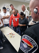 Al Hartmann  |  The Salt Lake Tribune Law enforcement officers listen to simulated sounds (voices) of what mentally ill people might hear in everyday life while performing other training excercises. They are memorizing the objects on the table and later writing down a detailed description of all the objects minutes later with the simulated voices playing.  The purpose of Thursday's training was to gain an understanding and empathy for dealing with the mentally ill in the course of their jobs.