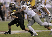 Arizona State quarterback Taylor Kelly, left, is pressure by Oregon linebacker Derrick Malone (22)  during the second half of an NCAA college football game, Thursday, Oct. 18, 2012, in Tempe, Ariz.  (AP Photo/Matt York)