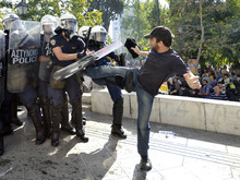 A protester clashes with riot police during a 24-hour nationwide general strike in Athens on Thursday, Oct. 18, 2012. Hundreds of youths pelted riot police with petrol bombs, bottles and chunks of marble Thursday as yet another Greek anti-austerity demonstration descended into violence. (AP Photo/Nikolas Giakoumidis)