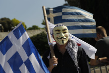 A protester with a mask and a Greek flag is seen during clashes during the 24-hour nationwide general strike in Athens on Thursday, Oct. 18, 2012. Hundreds of youths pelted riot police with petrol bombs, bottles and chunks of marble Thursday as yet another Greek anti-austerity demonstration descended into violence. (AP Photo/Kostas Tsironis)