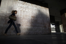 A pedestrian passes a sign of Greece's railways at the central train station of Athens during a 24-hour nationwide general strike on Thursday, Oct. 18, 2012. Labor unions in recession-hobbled Greece are holding another general strike against a new harsh austerity program, as European leaders beset by a deep debt crisis and economic stagnation gather for a summit meeting in Brussels. (AP Photo/Kostas Tsironis)