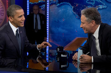 President Barack Obama talks with Jon Stewart during a taping of his appearance on