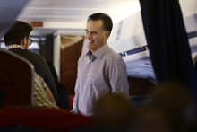 Republican presidential candidate, former Massachusetts Gov. Mitt Romney laughs as he talks with campaign trip director Charlie Pearce after boarding his campaign plane in Sterling, Va., Thursday, Oct. 18, 2012, enroute to New York City. (AP Photo/Charles Dharapak)