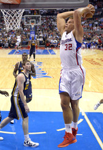 Los Angeles Clippers forward Blake Griffin, right, goes up for a dunk as Utah Jazz forward Gordon Hayward, second from left, and forward Paul Millsap look on during the first half of their preseason NBA basketball game, Wednesday, Oct.17, 2012, in Los Angeles.  (AP Photo/Mark J. Terrill)